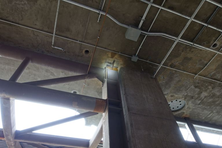 Inspecting structural steel columns; again, the concentrated beam can be seen in moderate daylight.